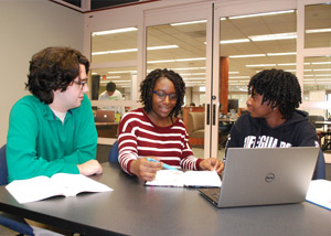 Three students studying together at the Writing Center in the Library